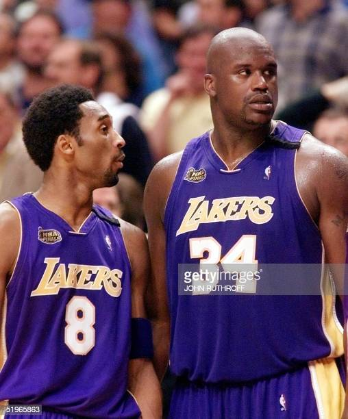 Shaquille O'Neal of the Los Angeles Lakers and teammate Kobe Bryant talk during a timeout 14 June in game four of the NBA Finals against the Indiana...