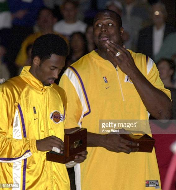 Shaquille O'Neal of the Los Angeles Lakers appears with his championship ring as teammate Kobe Bryant looks at his during a ceremony 01 November 2000...