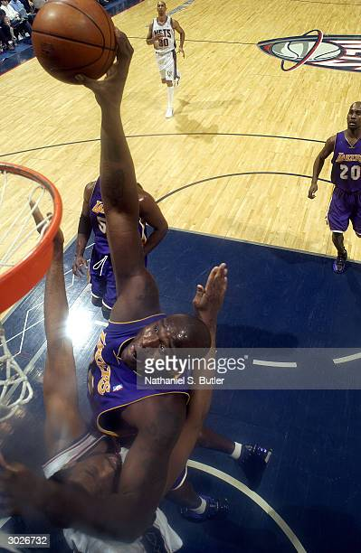 Shaquille O'Neal of the Los Angeles Lakers dunks over Jason Collins of the New Jersey Nets on February 29 2004 at Continental Airlines Arena in East...