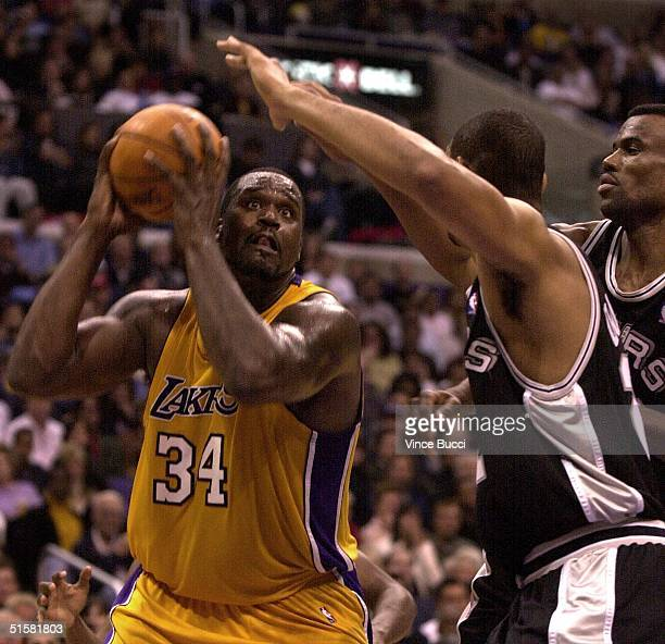 Shaquille O'Neal of the Los Angeles Lakers goes to the basket while being guarded by Tim Duncan and David Robinson of the San Antonio Spurs during...