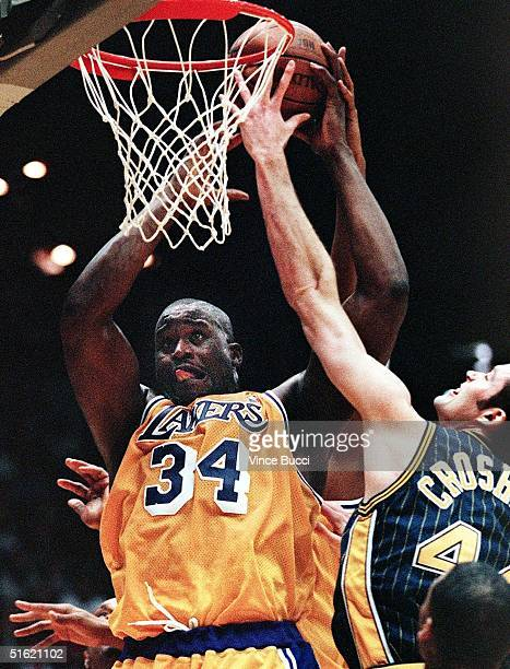 Shaquille O'Neal of the Los Angeles Lakers grabs a rebound over Austin Croshere of the Indiana Pacers during their 14 February game in Los Angeles Ca...