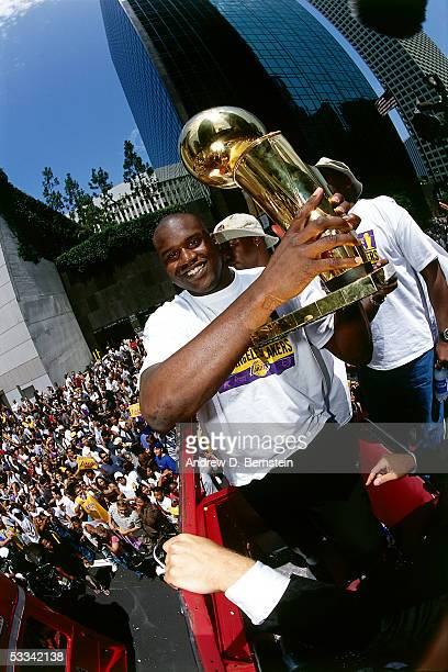 Shaquille O'Neal of the Los Angeles Lakers holds the NBA Championship Trophy during a parade after winning the 2000 NBA Finals against the Indiana...