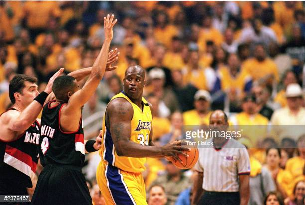 Shaquille O'Neal of the Los Angeles Lakers looks to move against Arvydas Sabonis and Steve Smith of the Portland Trail Blazers during Game 7 of the...