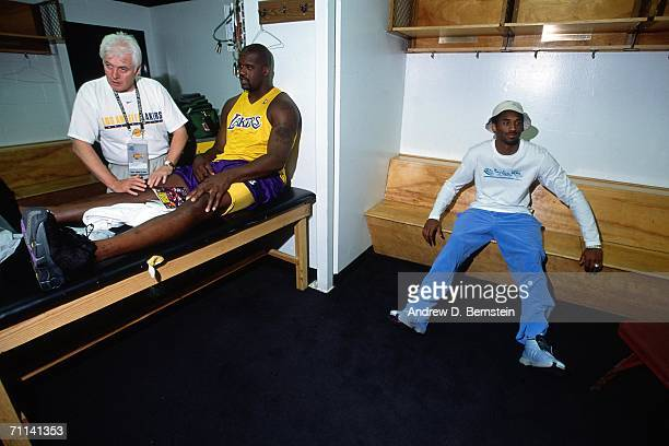 Shaquille O'Neal of the Los Angeles Lakers receives treatment in the locker room while talking to teammate Kobe Bryant of the Los Angeles Lakers...
