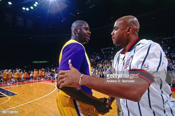 Shaquille O'Neal of the Los Angeles Lakers shakes hands with Charles Barkley of the Houston Rockets on October 22 1996 at the Great Western Forum in...