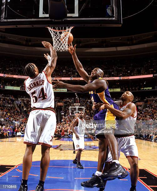 Shaquille O'Neal of the Los Angeles Lakers under pressure from Brian Skinnner and Derrick Coleman of the Philadelphia 76ers goes up for the shot...