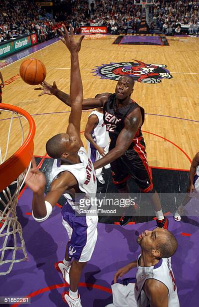Shaquille O'Neal of the Miami Heat goes to the basket against Chris Bosh and Loren Woods of the Toronto Raptors on December 12 2004 at Air Canada...
