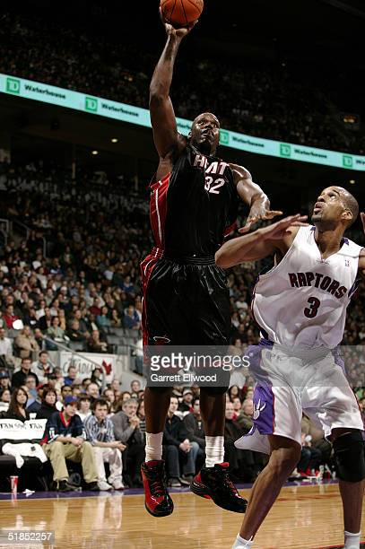Shaquille O'Neal of the Miami Heat goes to the basket against Loren Woods of the Toronto Raptors on December 12 2004 at Air Canada Centre in Toronto...