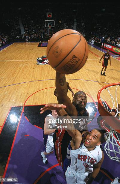Shaquille O'Neal of the Miami Heat takes the ball to the basket over Loren Woods of the Toronto Raptors during a game at Air Canada Centre on January...