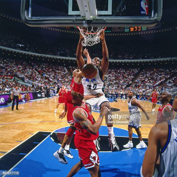 Shaquille O'Neal of the Orlando Magic dunks against Dennis Rodman of the Chicago Bulls during the third period of the game at the Orlando Arena on...