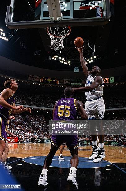 Shaquille O'Neal of the Orlando Magic goes up for a shot over Antoine Carr of the Utah Jazz during the game on March 14 1995 at Orlando Arena in...