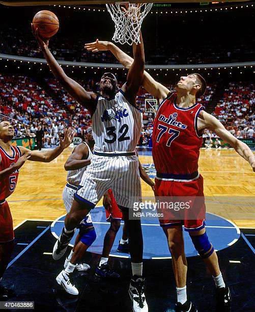 Shaquille O'Neal of the Orlando Magic shoots against Gheorghe Muresan of the Washington Bullets on April 17 1995 at the Amway Arena in Orlando...