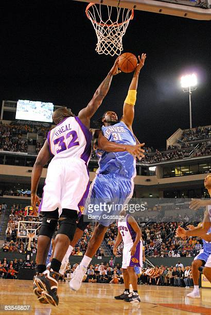 Shaquille O'Neal of the Phoenix Suns blocks a shot by Nene of the Denver Nuggets during a preseason game at the Indian Wells Tennis Garden on October...
