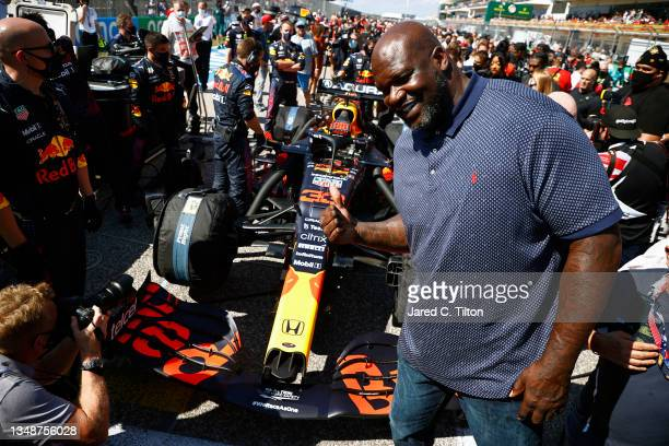 Shaquille O'Neal poses for a photo with the car of Max Verstappen of Netherlands and Red Bull Racing on the grid before the F1 Grand Prix of USA at...