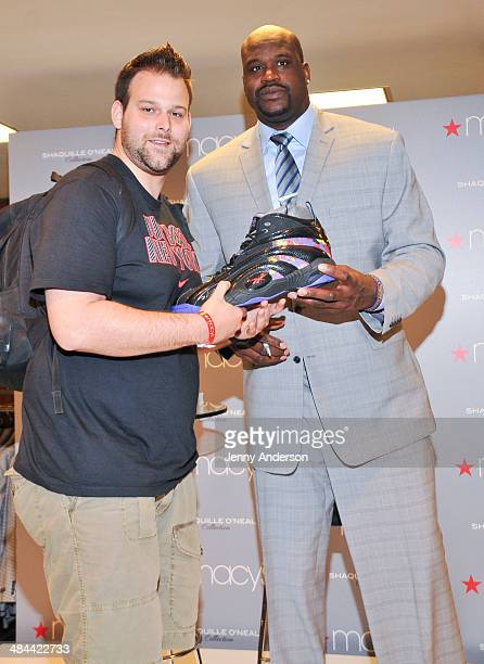 Shaquille O'Neal presents a fan with one of his size 22 shoes at the collection launch of his new men's clothing line at Macy's Herald Square on...