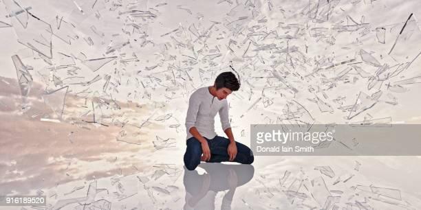 Shards of glass surrounding kneeling man