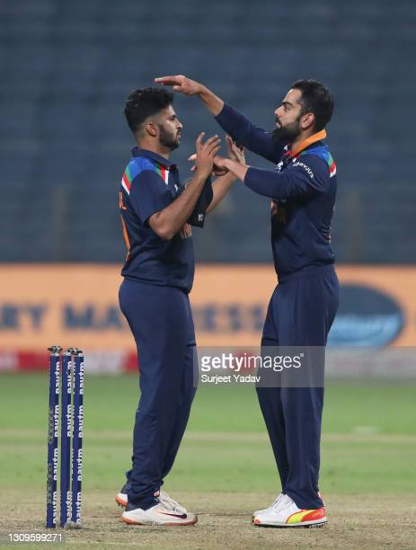 Shardul Thakur and Virat Kohli of India interact following the 3rd One Day International match between India and England at MCA Stadium on March 28,...