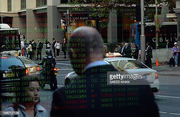 Share rates reflect on the window glass panel of the Australia Stocks Exchange in down town Sydney on May 7 2013 Australia's central bank cut...