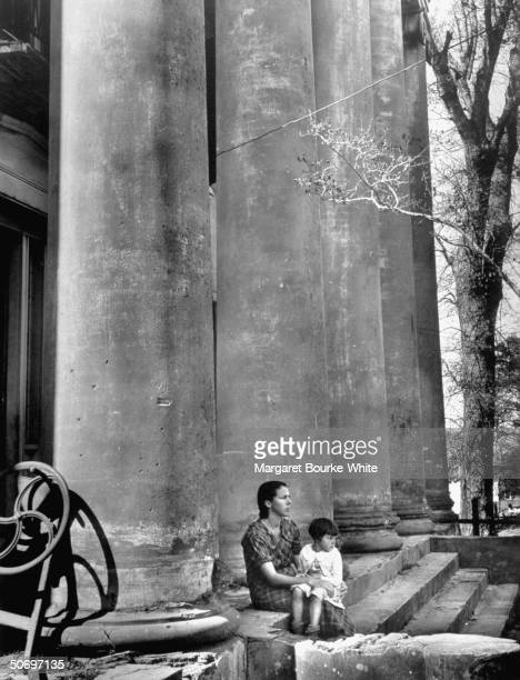 Sharecropper's wife young daughter sitting on the steps of rundown nearly abandoned antebellum mansion in which they rent 2 rooms for $5 a month on...
