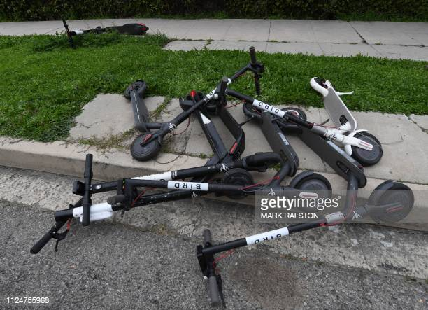 Shared electric scooters lie on a sidewalk in Los Angeles California on February 13 2019 Cities across the US are grappling with the growing trend of...