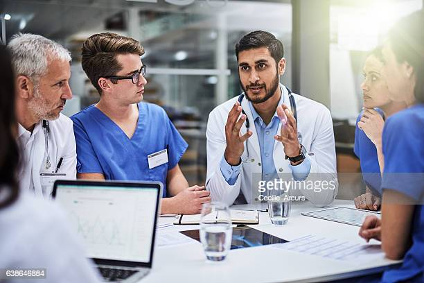 shared medical knowledge benefits his coworkers and patients - group of doctors stock pictures, royalty-free photos & images