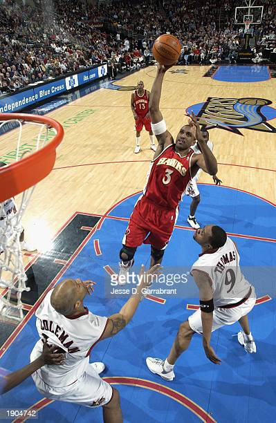 Shareef AbdurRahim of the Atlanta Hawks goes up for the shot against Kenny Thomas and Derrick Coleman of the Philadelphia 76ers during the NBA game...
