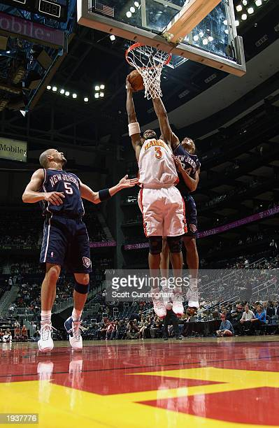 Shareef AbdurRahim of the Atlanta Hawks takes the ball to the basket against Richard Jefferson of the New Jersey Nets during the game at Philips...