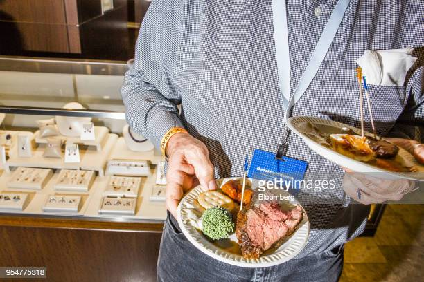 A shareholder holds plates of food during a Borsheims Cocktail Reception ahead of the Berkshire Hathaway Inc annual meeting in Omaha Nebraska US on...