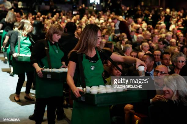 Shareholders are handed cups of coffee for an audience tasting during the Starbucks Annual Meeting of Shareholders at McCaw Hall in Seattle...