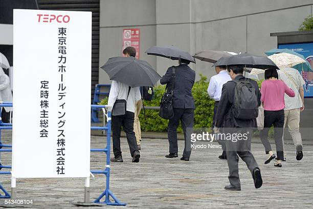 Shareholders in Tokyo Electric Power Company Holdings Inc head to the venue of their general meeting in Tokyo on June 28 2016 While shareholders...