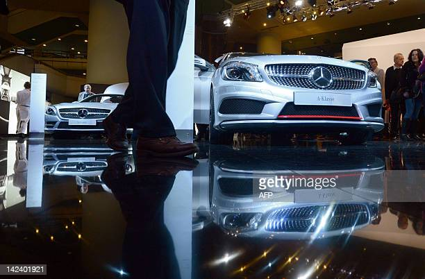 Shareholders inspect Mercedes cars of German automaker Daimler at the venue where is taking place the Daimler AG's annual general meeting in Berlin...