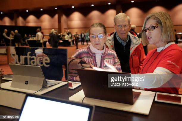 Shareholders look at the Microsoft Surface during the annual Microsoft shareholders meeting in Bellevue Washington on November 29 2017 / AFP PHOTO /...