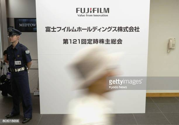 Shareholders of Fujifilm Holdings Corp head for their general meeting in Tokyo on June 29 after accounting irregularities were found at its overseas...