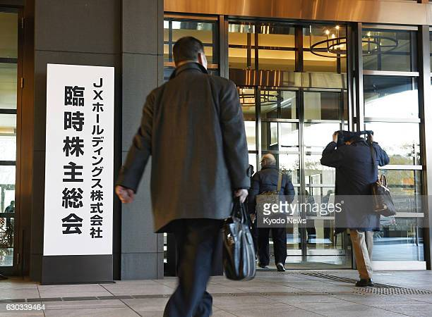Shareholders of Japan's largest oil refiner JX Holdings Inc arrive at the venue for its extraordinary shareholders' meeting in Tokyo on Dec 21 to...