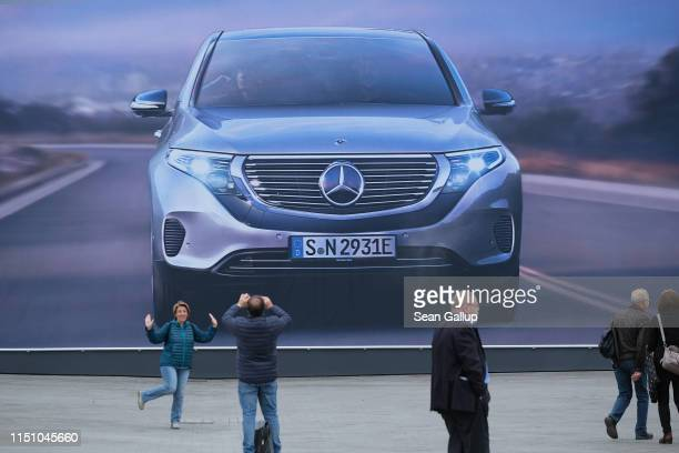 Shareholders snap photos outside the annual Daimler AG shareholders meeting on May 22, 2019 in Berlin, Germany. Daimler has struggled with falling...