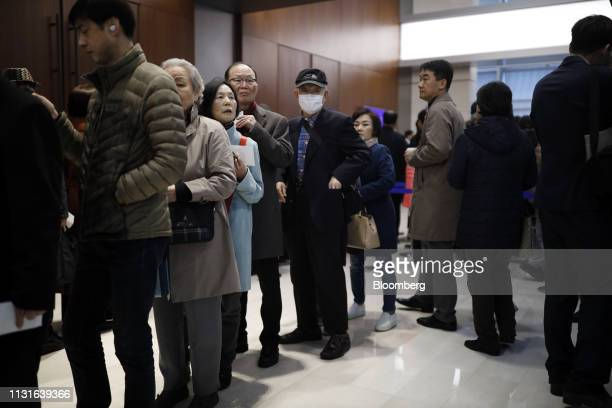 Shareholders stand in line for the Samsung Electronics Co annual general meeting at the company's Seocho office building in Seoul South Korea on...