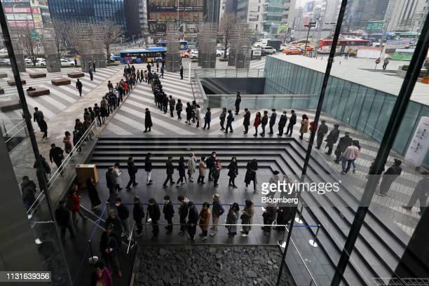 Shareholders stand in line to enter the Samsung Electronics Co annual general meeting outside the company's Seocho office building in Seoul South...