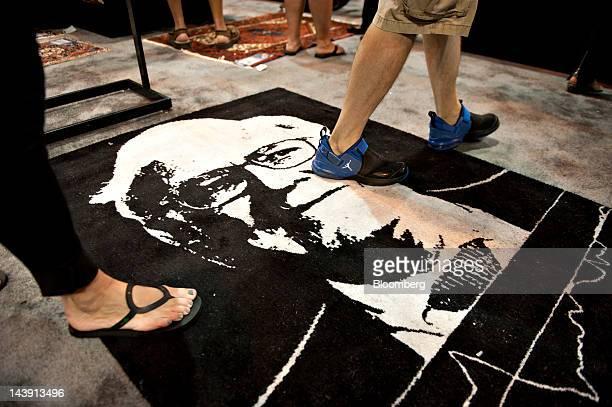 Shareholders walk over a carpet bearing an image of Warren Buffett chairman of Berkshire Hathaway Inc during the Berkshire Hathaway annual...