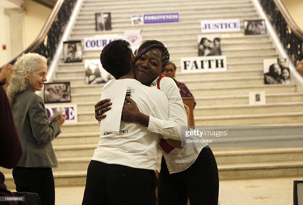 Sharell Jacobs, right, whose niece, Paula Jacobs, was killed last month, gets a hug from fellow survivor Isaura Mendes who lost two sons to violence, after Jacobs delivered a survivor tribute, during the 11th Annual Survivors of Homicide Victims Awareness Month ceremonies to honor survivors of homicide victims at the Statehouse Monday.