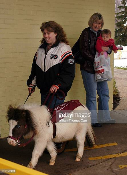 Shari Bernstiel is helped along the sidewalk by Tonto her guide horse as a woman and child watch March 19 2004 in Lansdale Pennsylvania Tonto a...