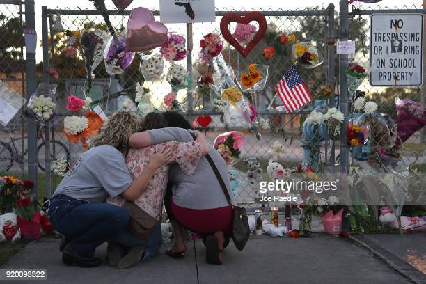 Shari Unger Melissa Goldsmith and Giulianna Cerbono hug each other as they visit a makeshift memorial setup in front of Marjory Stoneman Douglas High...