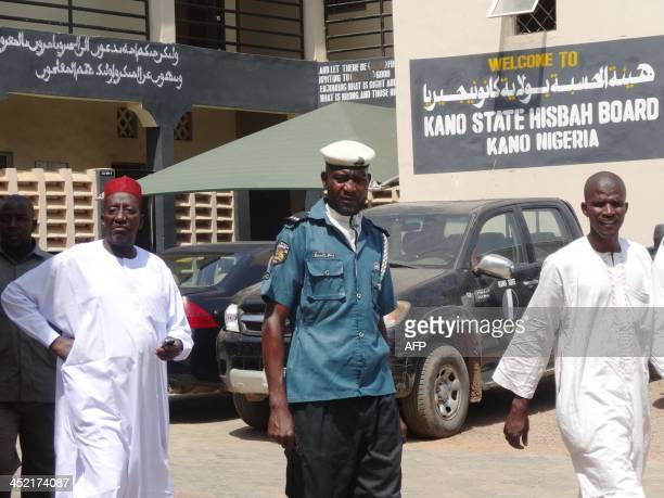 A sharia enforcer called Hisbah in full uniform walks between two men in the Hisbah headquarters in the northern Nigerian city of Kano on October 28...