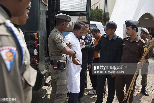 Sharia police escort an unidentified Acehnese man in preparation for public caning at the Munawarah Jantho mosque compound in Aceh Besar district in...