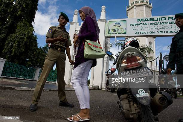 A Sharia police man requests to check the identity of an Acehnese woman in tight pants in Banda Aceh on November 14 2012 Indonesia's constitution...