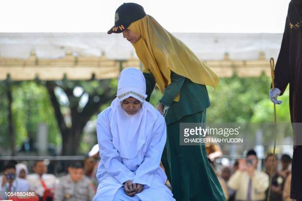 A Sharia police officer places a 21year old Muslim woman for public caning after being caught in close proximity with her boyfriend in Banda Aceh on...