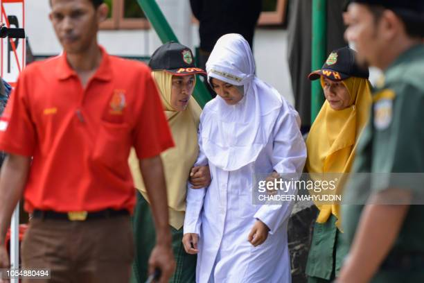Sharia police officers escort a 21year old Muslim woman for public caning after being caught in close proximity with her boyfriend in Banda Aceh on...