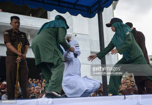 Sharia police officers prepare a woman to be publicly flogged in front of a mosque in the provincial capital Banda Aceh on April 20 2018 A group of...