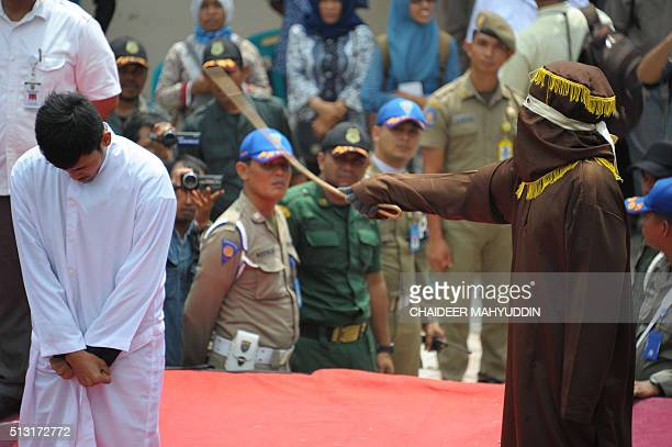 A sharia policeman canes a man for breaking Islamic law during a public punishment in Banda Aceh on March 1 2016 The man who had been caught spending...