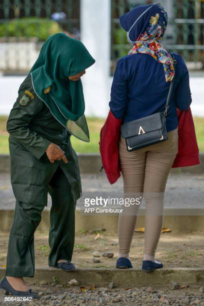 A Sharia policewoman look at the pants of a woman during a sharia law inspection in Banda Aceh Aceh province on October 26 2017 Aceh on Sumatra...