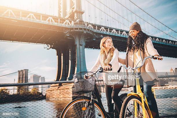 sharing a bicycle ride my friend in nyc - brooklyn new york stock photos and pictures